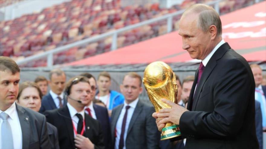 El presidente ruso, Vladimir Putin, sostiene la copa del mundo en la ceremonia de inauguración del Mundial de Rusia 2018 en el estadio Luzhniki de Moscú.