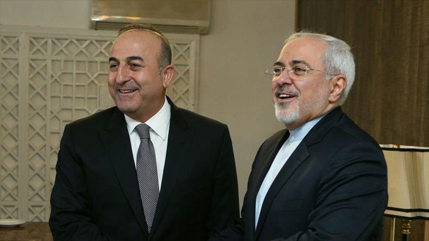 El canciller de Irán, Mohamad Yavad Zarif, (drcha.) estrecha la mano de su par turco, Mevlut Cavusoglu.