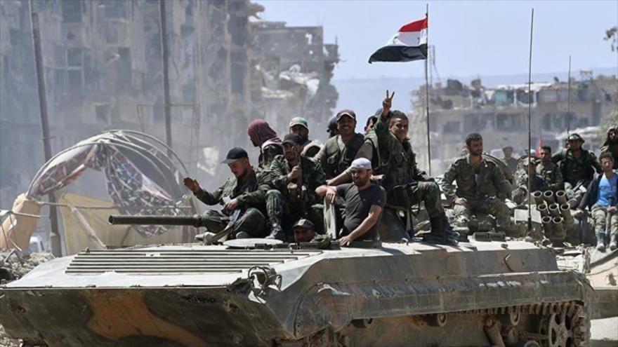 Las fuerza sirias festejan avances del Ejército ante terroristas en el campamento de refugiados palestinos de Al-Yarmuk, sur de Damasco, la capital.