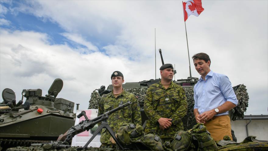 El premier de Canadá, Justin Trudeau, observa equipamiento militar junto a varios efectivos de las tropas de la OTAN en Letonia, 10 de julio de 2018.