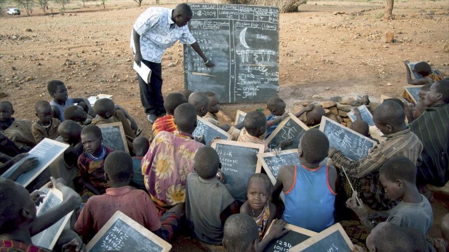 Un profesor da clases en Uganda a varios alumnos que usan pizarras en lugar de cuadernos por ser una opción más barata