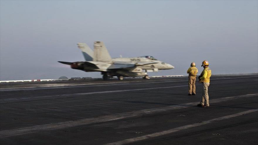 Avión de la coalición anti-EIIL se dispone a despegar de un portaviones para realizar ataques en Siria.
