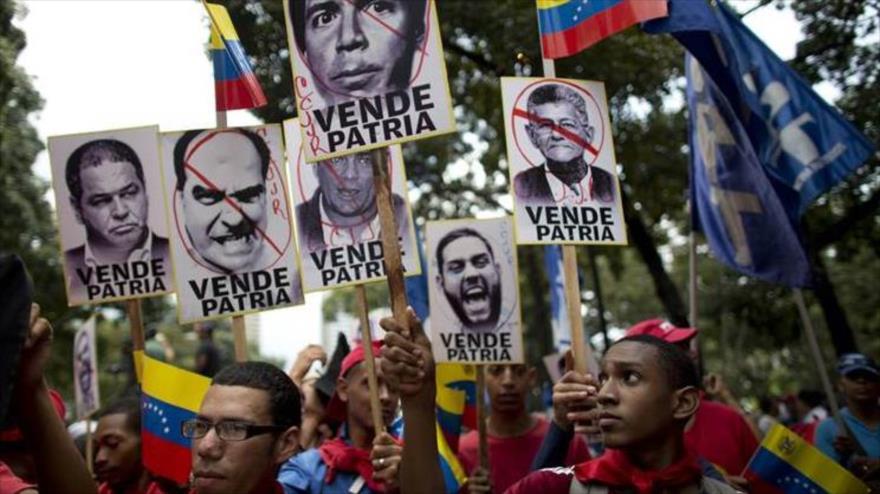 Simpatizantes del presidente venezolano, Nicolás Maduro, portan en una marcha imágenes de líderes opositores, Caracas, 12 de septiembre de 2017.