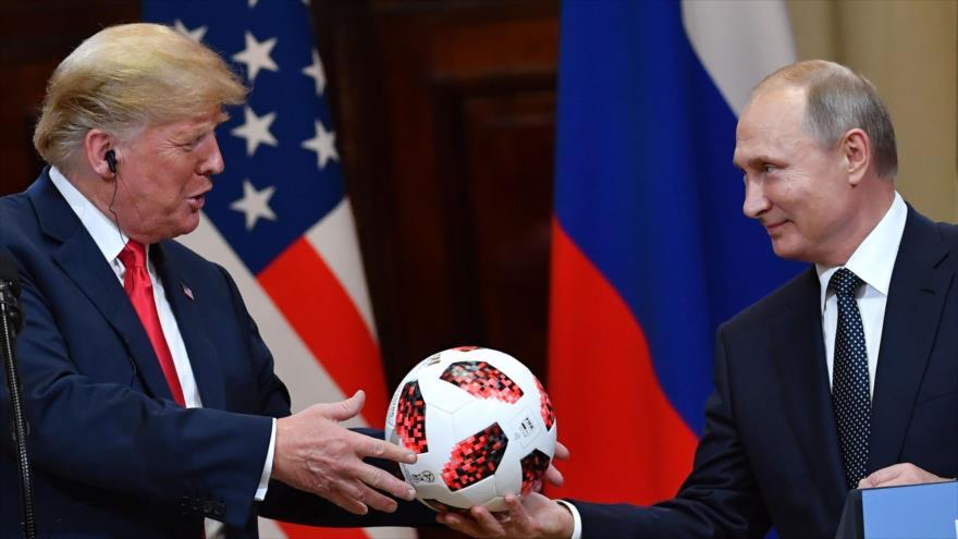 El presidente ruso, Vladimir Putin, le regala a su par estadounidense, Donald Trump, una pelota en una rueda de prensa en Helsinki, 16 de julio de 2018.