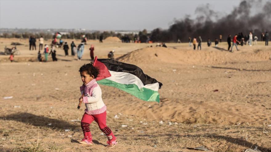 Un niño palestino lleva la bandera nacional de Palestina en una manifestación en la Franja de Gaza, 14 de mayo de 2018.