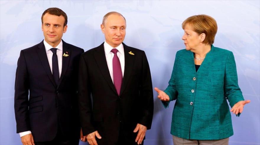 De izq. a dcha.: El presidente francés, Emmanuel Macron, su par ruso, Vladimir Putin, y la canciller alemana, Angela Merkel.