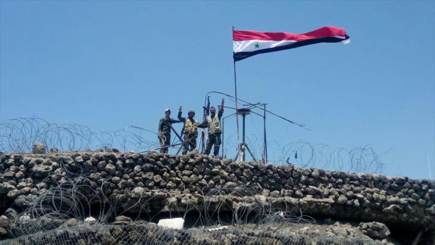 Soldados del Ejército sirio enarbolan su bandera nacional en la cima de una colina conocida como Tallet Al-Hara en Daraa, 17 de julio de 2018.