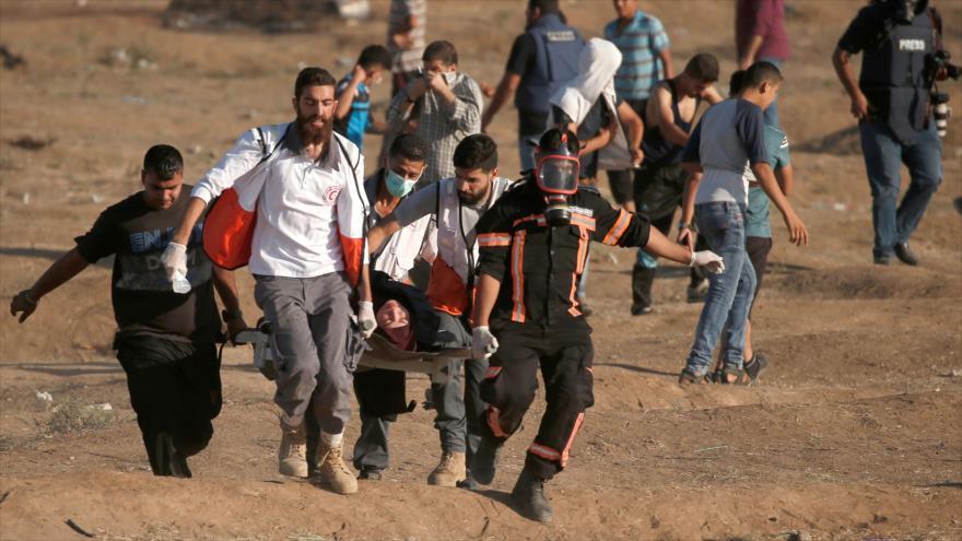 Palestinos movem uma mulher ferida durante um protesto na Faixa de Gaza, em 27 de julho de 2018.