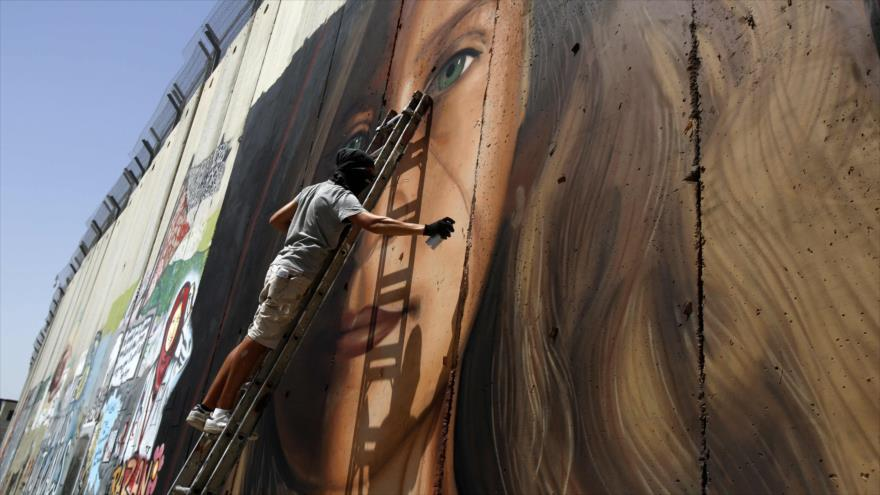El artista italiano Jorit Agoch pinta el retrato de de la adolescente palestina Ahed Tamimi sobre el muro de separación en la ocupada Cisjordania.
