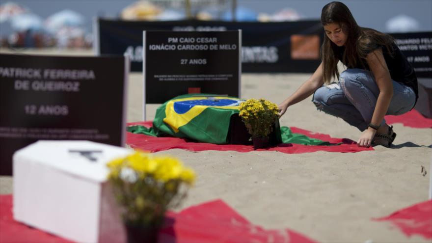 Una mujer coloca flores en un ataúd durante una protesta contra la violencia en Río de Janeiro.