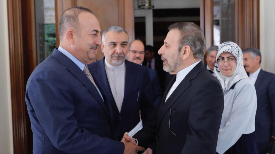 El canciller turco, Mevlüt Çavuşoğlu (izda.) le da la mano al Mahmud Vaezi, enviado especial del presidente iraní, en Ankara, 9 de agosto de 2018.