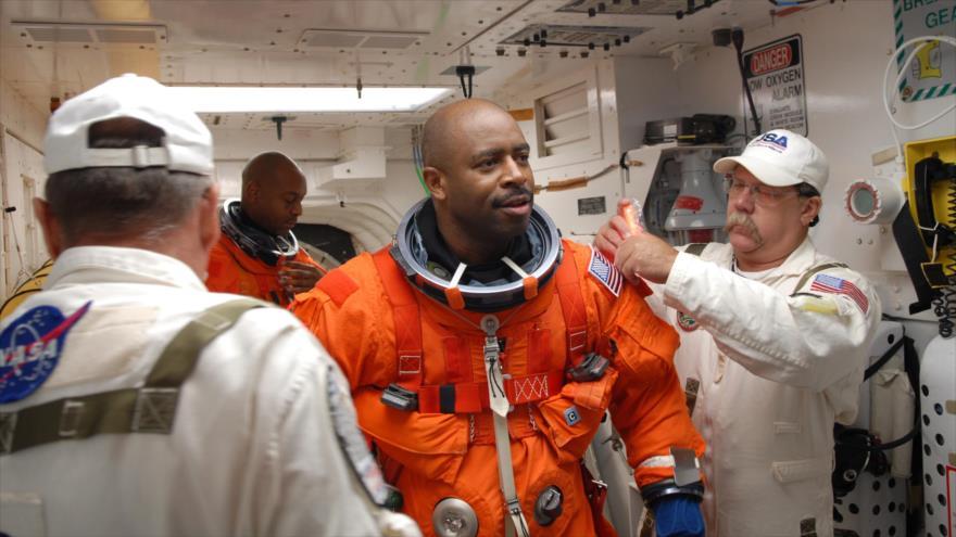 Leland Melvin (Centro), el astronauta de la NASA se prepara para una misión.