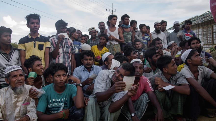 Refugiados rohingyas hacen cola en un centro de distribución de ayuda en un campo de refugiados en Bangladés, 12 de agosto de 2018. Foto: AFP