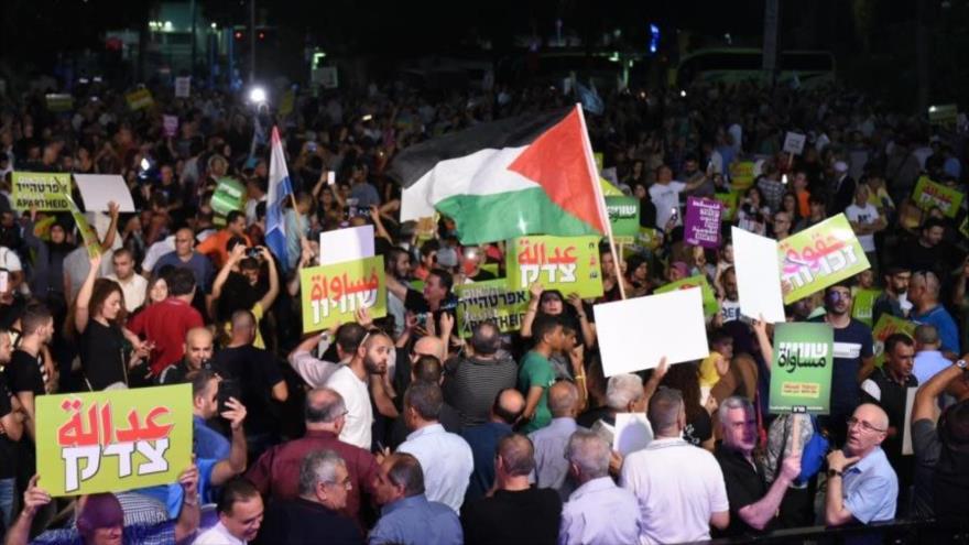 Israelíes ondean la bandera palestina en una protesta en Tel Aviv contra la ley de estado-nación judío, 11 de agosto de 2018.