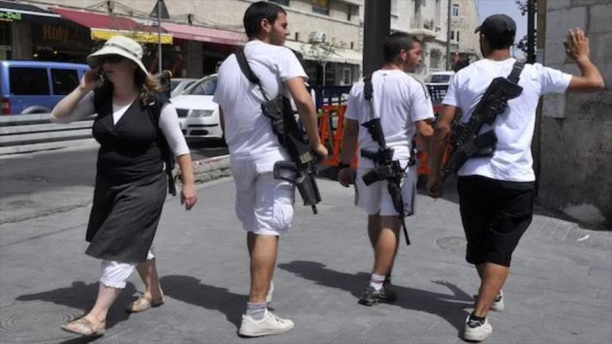 Israelíes que portan rifle de asalto en territorios palestinos ocupados.