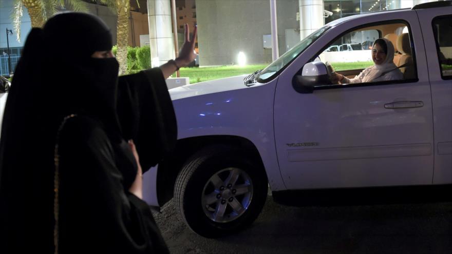 Una mujer saudí muestra la señal de victoria a otra conduciendo su coche en Riad (capital de Arabia Saudí), 24 de junio de 2018. (Foto: AFP)