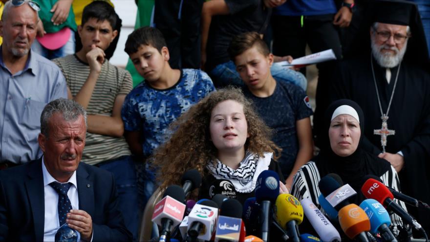 La joven palestina Ahed Tamimi (C) sentada en medio de sus padres ofrece una conferencia de prensa, 29 de julio de 2018. (Foto: AFP)
