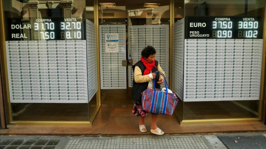 Una mujer sale de una oficina de cambio de moneda en el distrito financiero de Buenos Aires, capital argentina.