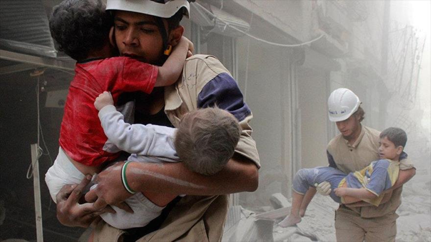 Los llamados cascos blancos fotografiados mientras llevan a dos niños en una localidad en Idlib, Siria.