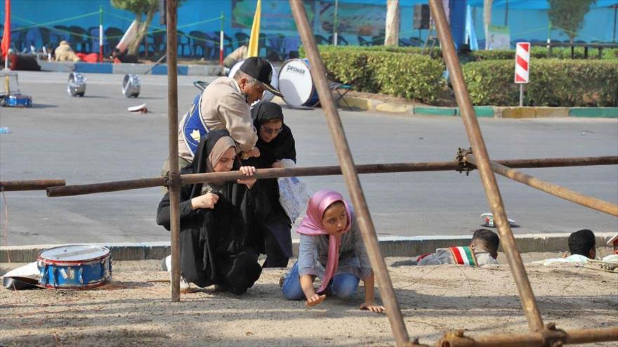 Un agente militar ayuda a varias personas durante un atentado terrorista en Ahvaz, suroeste de Irán, 22 de septiembre de 2018. (Foto: IRNA)