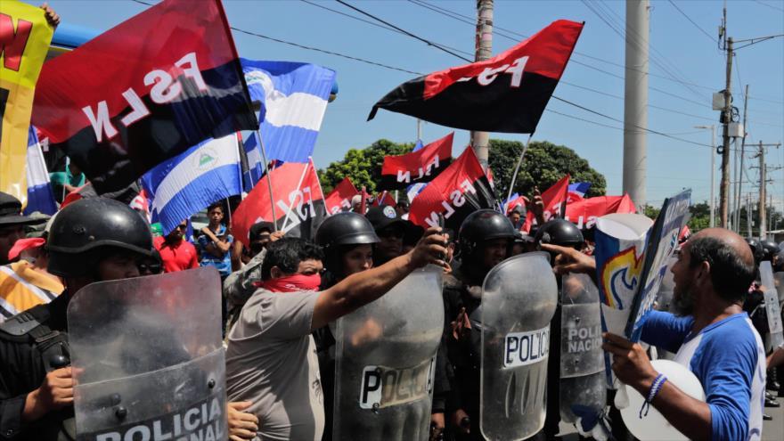 Grupo de simpatizantes sandinistas respaldan a la policía antidisturbios en una protesta opositora en Managua, 9 de septiembre de 2018. (Foto: AFP)