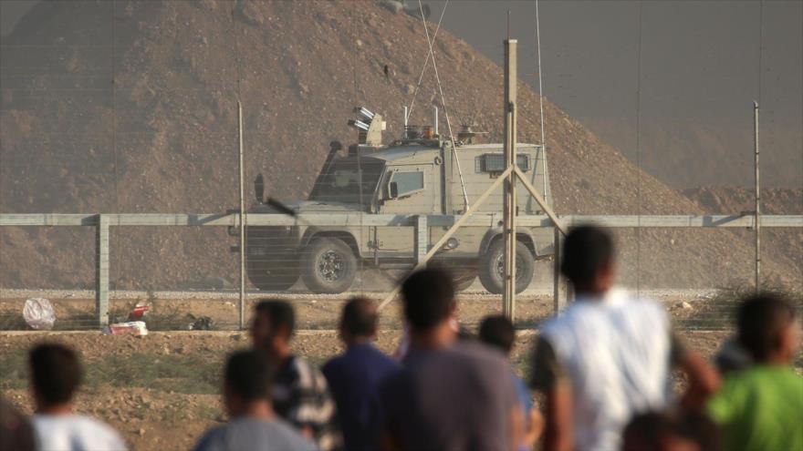 Los manifestantes palestinos observan un vehículo de las fuerzas israelíes a lo largo de la frontera con Gaza, 28 de septiembre de 2018. (Foto: AF)