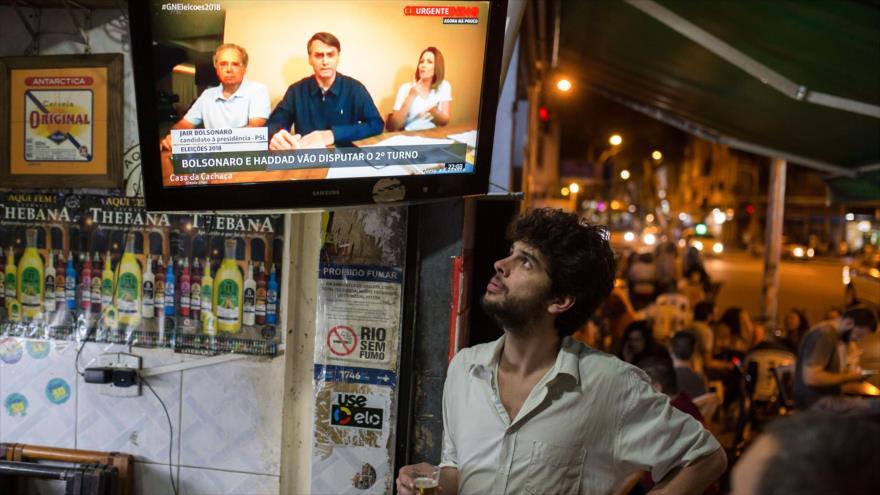 La gente escucha las declaraciones del candidato presidencial Jair Bolsonaro en un bar en Río de Janeiro, Brasil, 7 de octubre de 2018. (Foto AFP)