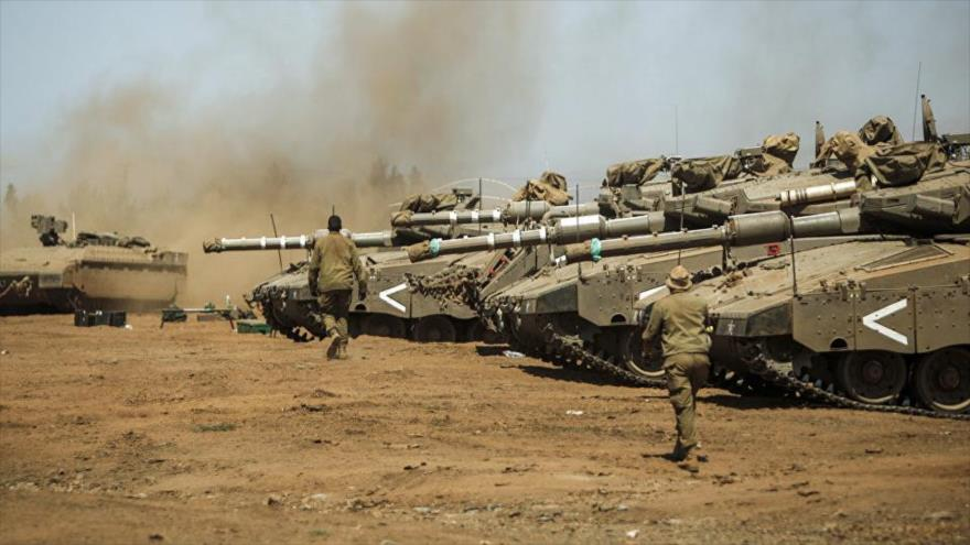 Soldados israelíes pasan junto a tanques modelo Merkava Mark IV del ejército de Israel en una maniobra militar.