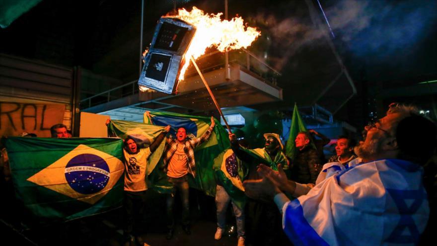 Seguidores del ultraderechista Jair Bolsonaro incendian un modelo de dispositivo de votación electrónico, Sao Paulo, 7 de octubre de 2018. (Foto: AFP).