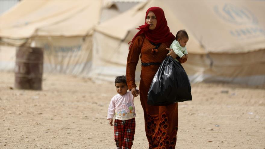 Una mujer siria desplazada de Deir Ezzor (este de Siria) camina con sus hijos en un campamento de refugiados, 8 de octubre de 2018. (Fuente: AFP)