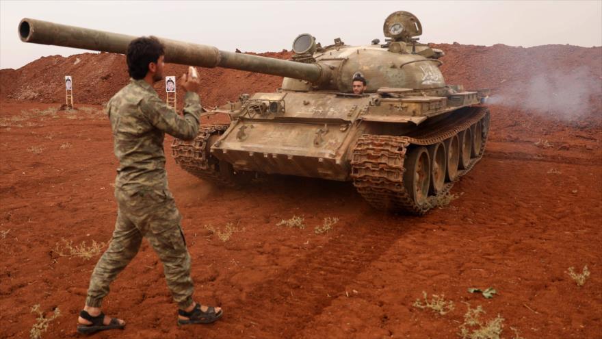 Llamados rebeldes sirios del Frente de Liberación Nacional (FLN) llevan un tanque y sus armas pesadas en las afueras de Idlib. 9 de octubre de 2018. (Foto: AFP)