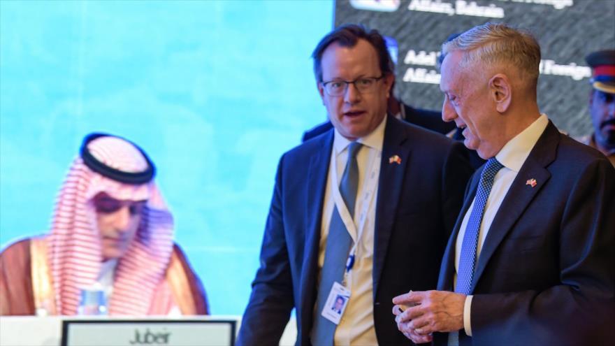 James Mattis pasa por delante de una pantalla en la que se muestra al canciller saudí, Adel al-Yubeir, Manama, 27 de octubre de 2018. (Foto: AFP)