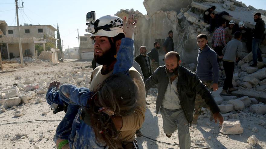 Un miembro de los llamados cascos blancos ayuda a un civil.