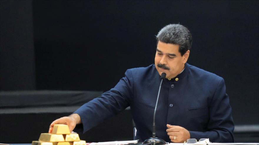 El presidente de Venezuela, Nicolás Maduro, toca un lingote de oro durante un discurso en Caracas, 22 de marzo de 2018. (Foto: AFP)