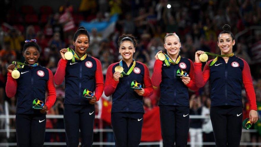 Cinco gimnastas estadounidenses muestran su medalla de oro.