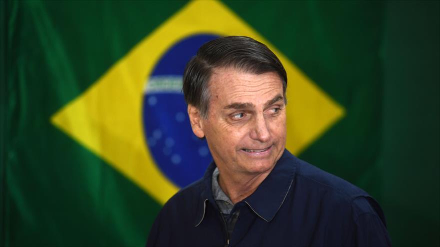 Jair Bolsonaro, presidente electo de Brasil, camina frente a la bandera nacional durante los comicios, Río de Janeiro, 7 de octubre de 2018. (Foto: AFP)