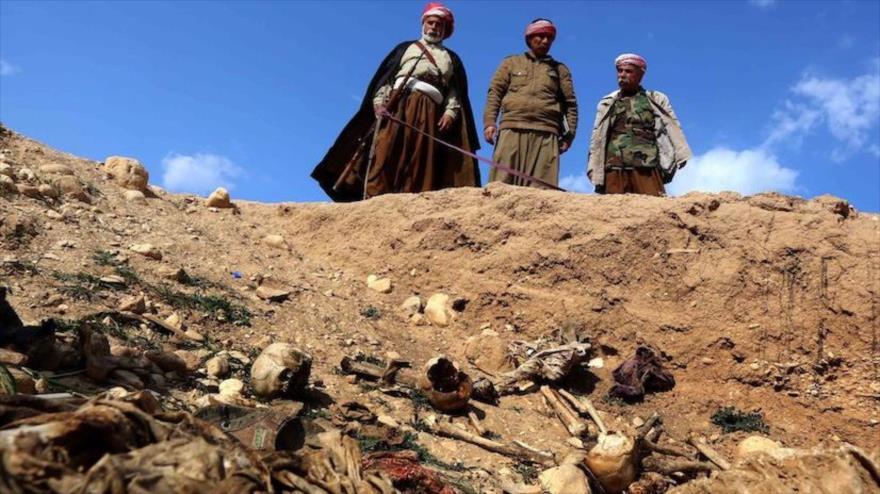 Varios iraquíes observan restos humanos encontrados en una fosa común dejado por los terroristas del EIIL.