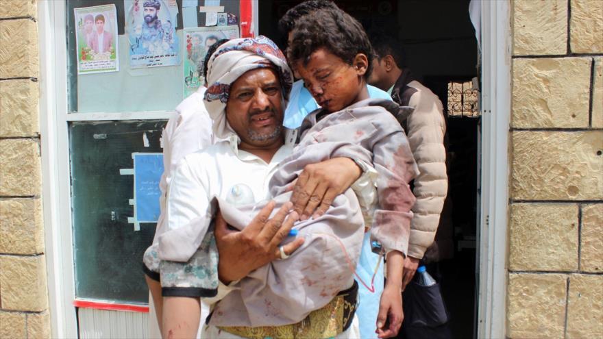 Un combatiente del movimiento popular yemení Ansarolá traslada a un niño herido en un ataque saudí.