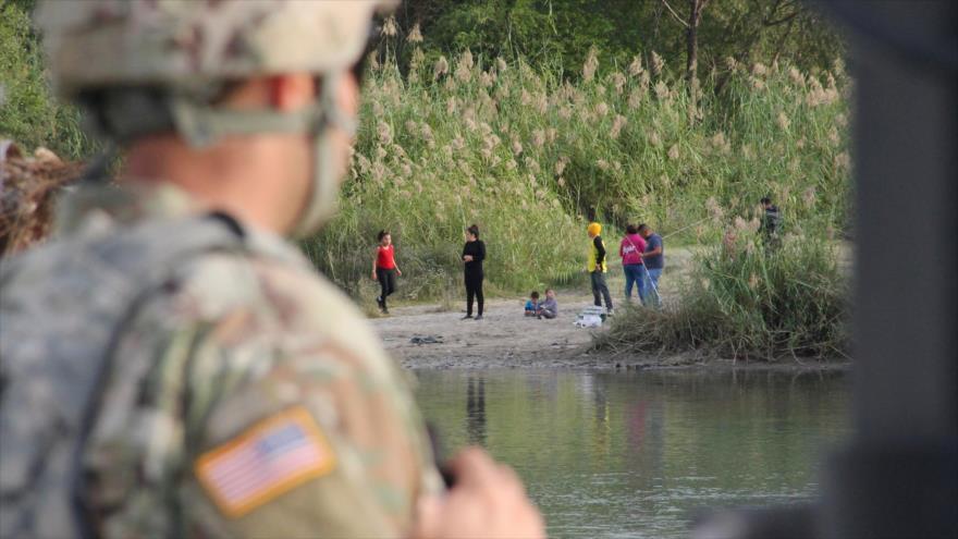 Un soldado estadounidense mira a un grupo de inmigrantes en la frontera sur con México, 17 de noviembre de 2018. (Foto: AFP)