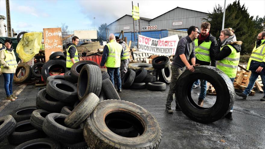 """Integrantes de los """"chalecos amarillos"""" levantan una barricada en Montabon, noroeste de Francia, 4 de diciembre de 2018. (Fuente: AFP)"""