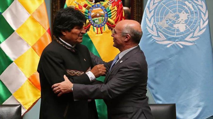 El coordinador residente de la ONU en Bolivia, Mauricio Ramírez (dcha.), saluda efusivamente al presidente boliviano, Evo Morales, en un acto público.