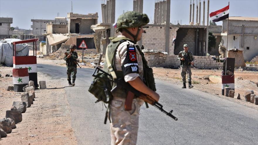 Soldados rusos y sirios hacen guardia en el cruce de Abu Duhur, en el este de la provincia siria de Idlib, 25 de septiembre de 2018. (Foto: AFP)