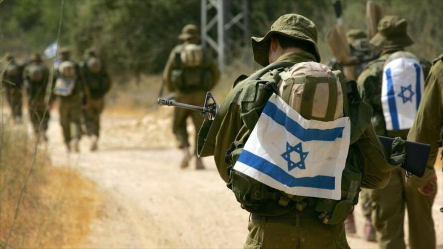 Fuerzas militares israelíes caminando en un sendero con evidentes signos de cansancio.