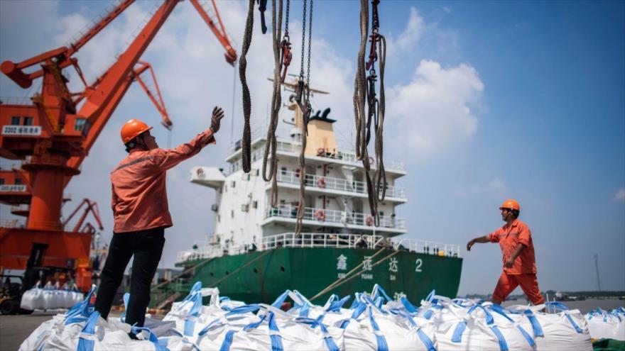 Obreros descargan bolsas de productos químicos en un puerto de Zhangjiagang, en la provincia oriental china de Jiangsu, 7 de agosto de 2018.
