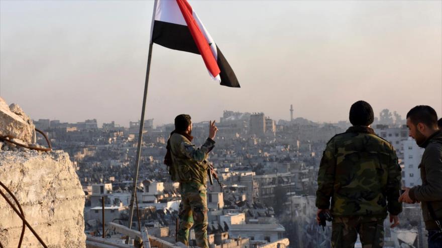 Un soldado sirio gesticula un signo de victoria (V) después de que el Ejército tomara control de un pueblo en la provincia de Alepo.