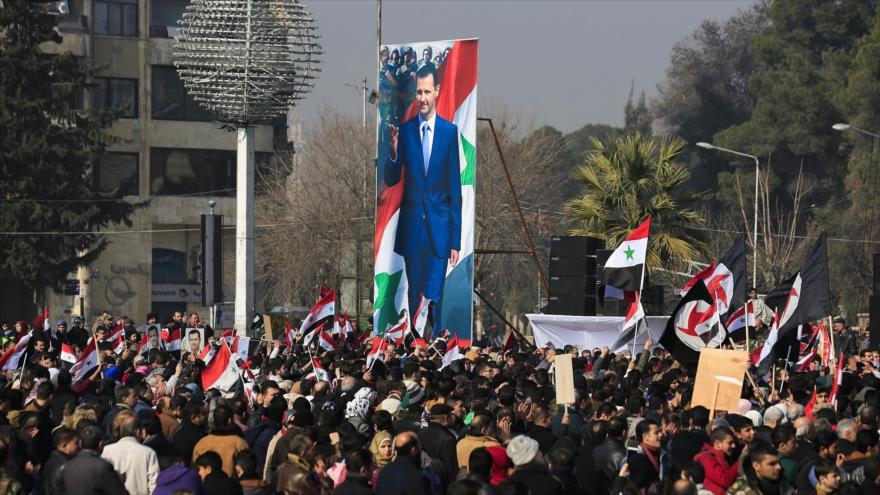 Simpatizantes del Gobierno sirio sostienen la bandera nacional y las imágenes del presidente Bashar al-Asad en Alepo, 19 de enero de 2017. (Foto: AP)