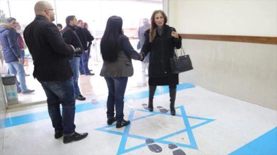 La ministra de Asuntos de Medios y Comunicaciones de Jordania, Jumana Ghunaimat, pisa la bandera israelí en una reunión oficial, diciembre de 2018.