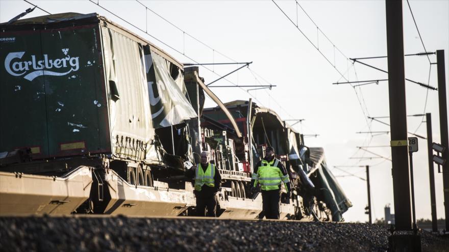 Hombres caminan frente a un tren de carga dañado después de un accidente en Nyborg, Dinamarca, 2 de enero de 2019. (Foto: AFP)