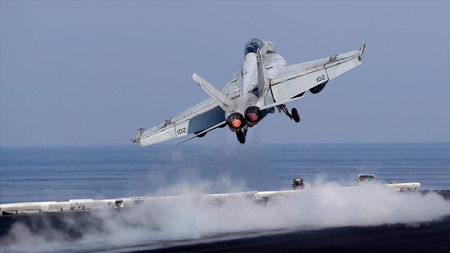 Un avión de combate de la llamada coalición anti-EIIL despega de un portaviones para bombardear suelo sirio.