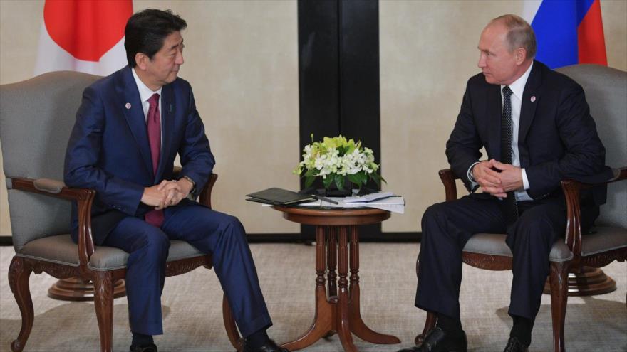 El presidente ruso, Vladimir Putin (dcha.), junto al primer ministro de Japón, Shinzo Abe, en Singapur, 14 de noviembre de 2018. (Foto: AFP)